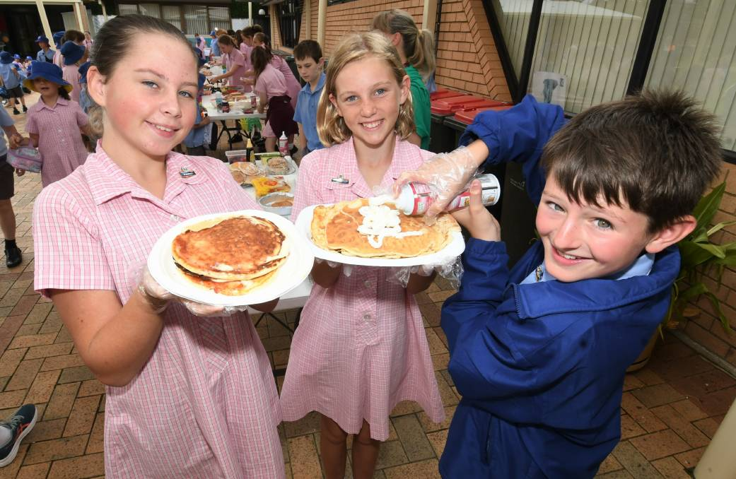 Year 6 students Isha Dopper, Anna Seaman and Felix Pike serving up pancakes on Shrove Tuesday at St Philomena's School. Photo: CHRIS SEABROOK 021621cshrove