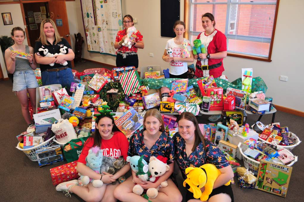 CHRISTMAS CHEER: Members of the MacKillop College Mercy and Justice Group with the toys and food items donated by the students.