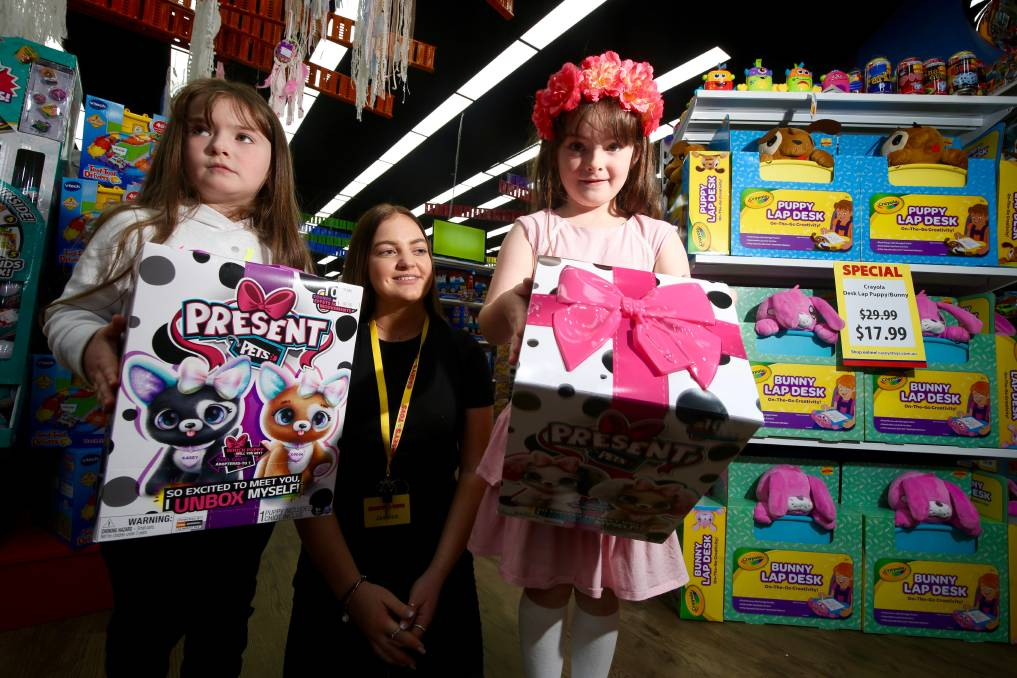 TOYS GALORE: Five-year-old Melissa Morris and Sarah Morris, six, with Casey's Toys shop assistant Jessica Belmont, showing off some Christmas gift ideas. Photo: PHIL BLATCH